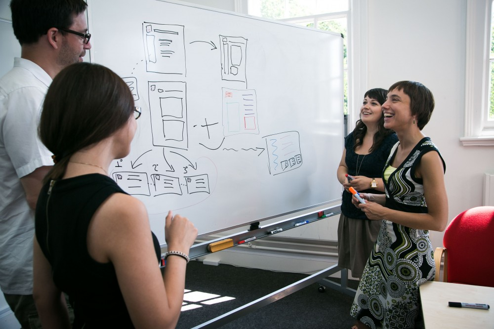 Designers standing around a whiteboard discussion some interfaces designs drawn on it.